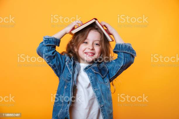 Little schoolgirl with book on her head wearing jeans jacket and picture id1188852481?b=1&k=6&m=1188852481&s=612x612&h=cw wz17btx3yd axmsdbob82qrt myfoqu8vxmj6v44=