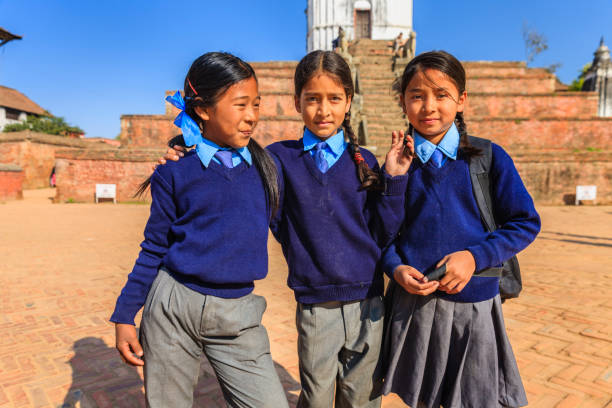 Little schoolgirls on Durbar Square in Bhaktapur, Nepal stock photo