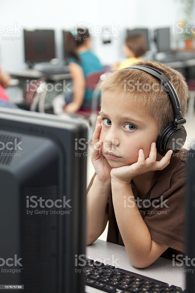Little serious boy in computer class with earphones royalty-free stock photo