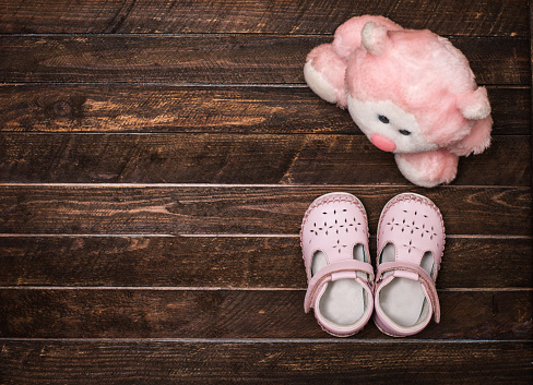 Little shoes and toy on wooden floor. Pair baby shoes. stock photo