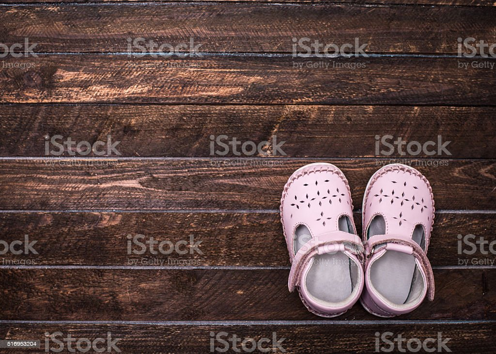Little shoes on dark wooden floor. Pair of baby shoes. stock photo