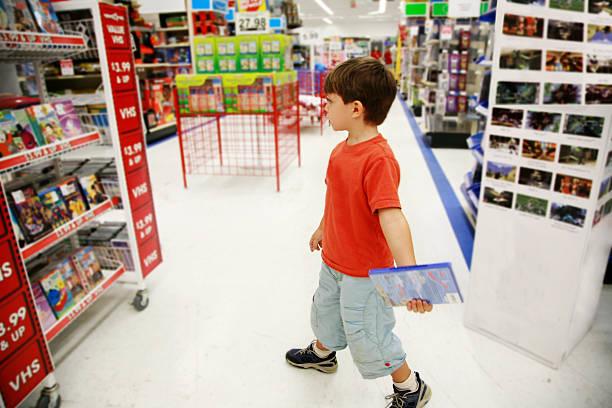 kleiner shopper im toy store - cd ständer stock-fotos und bilder