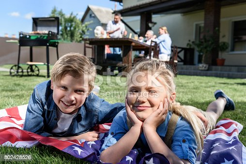 istock little siblings resting on american flag with family having picnic behind 802428526