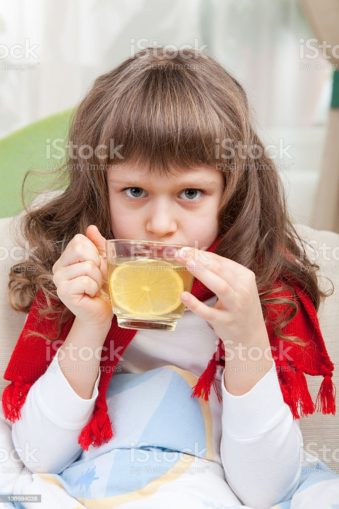 Little sick girl with scarf in bed is taking medicine Close-up sympathetic little sick girl wrapped in red scarf under blanket in bed is drinking antiviral with lemon slice from transparent cup Antipyretic Stock Photo