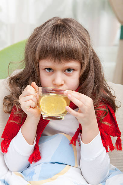 Little sick girl with scarf in bed is taking medicine Close-up sympathetic little sick girl wrapped in red scarf under blanket in bed is drinking antiviral with lemon slice from transparent cup antifebrile stock pictures, royalty-free photos & images