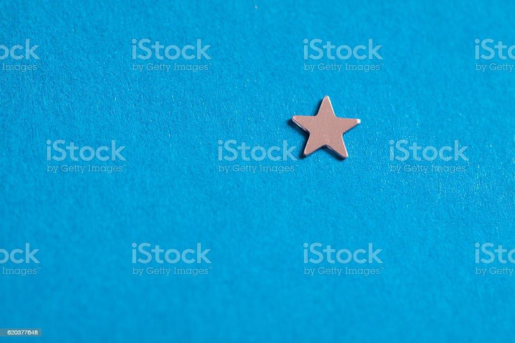 Little silver shiny star on blue background. zbiór zdjęć royalty-free