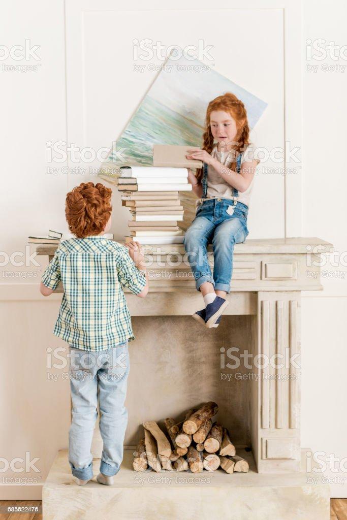 小妹妹和弟弟在壁爐邊玩書 免版稅 stock photo