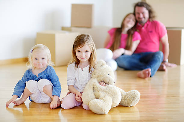 little sisters and their parents in new home - happy mom packing some toys stock photos and pictures