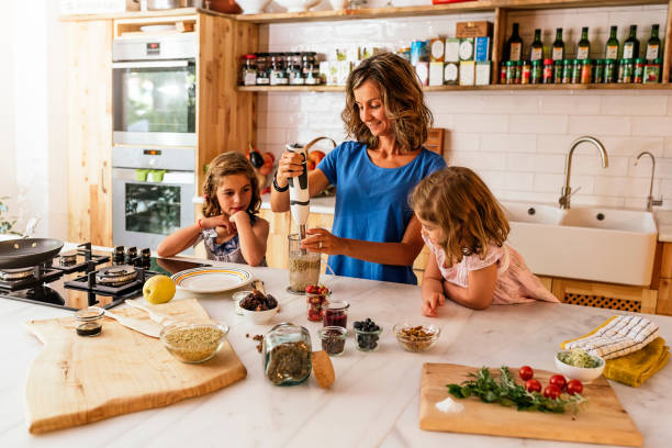 Little sisters cooking with her mother in the kitchen. Little sisters cooking with her mother in the kitchen. Infant Chef Concept. electric mixer stock pictures, royalty-free photos & images