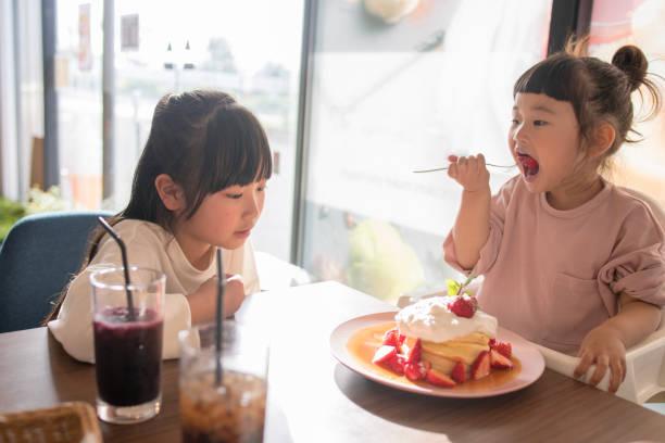 kleine schwestern heißen kuchen im café essen - innocent saft stock-fotos und bilder