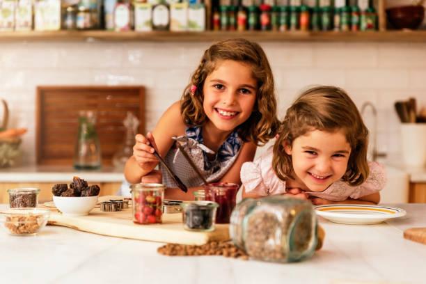 Little sisters girl preparing baking cookies. stock photo