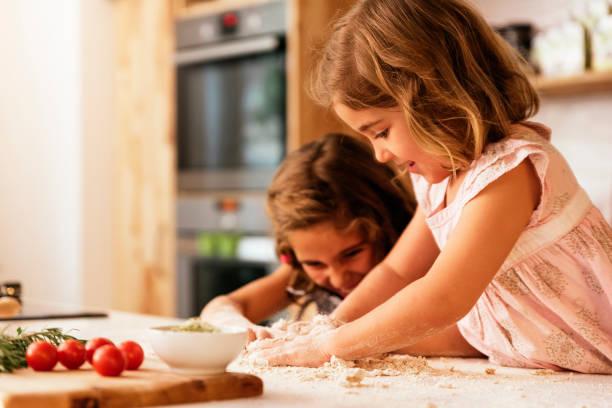 kleine schwestern mädchen vorbereitung backen cookies. - frucht pizza cookies stock-fotos und bilder