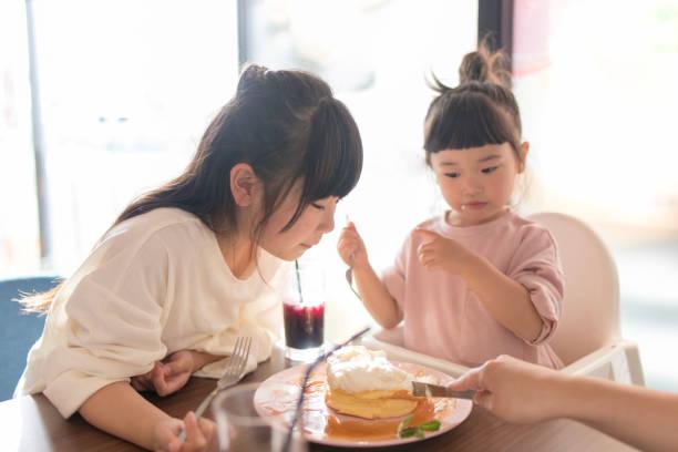 kleine schwestern glücklich essen pfannkuchen im café - innocent saft stock-fotos und bilder