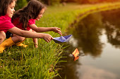 Cute twin girls putting paper boats on calm water of river while resting in park on summer day together