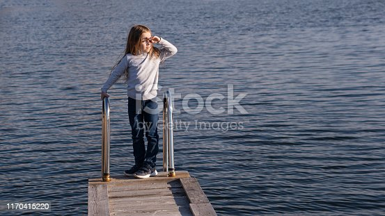 In harmony with nature, alone with himself. Little girl stands on a wooden pier near a wide river. She is looking at the sun. Hiking and adventure. Happy childhood, lifestyle concept