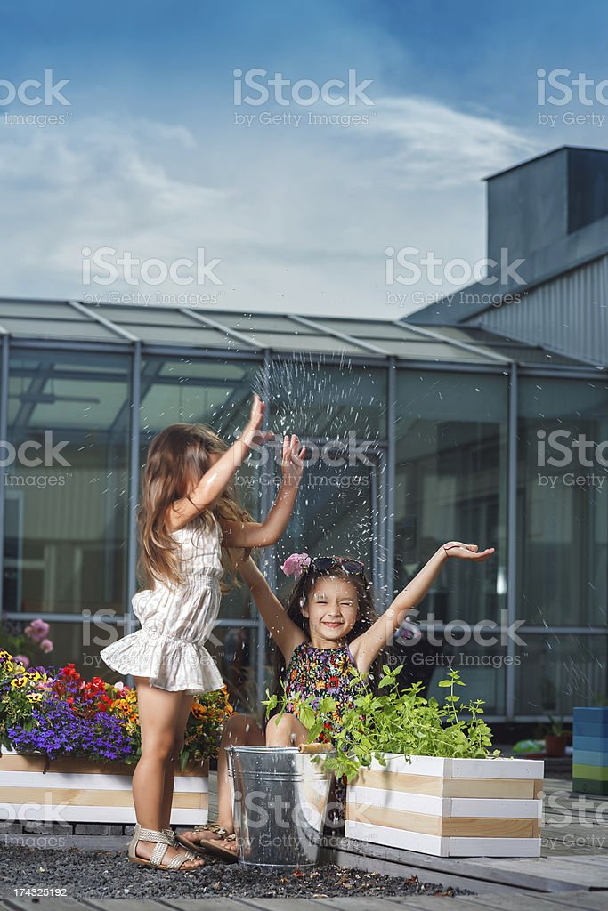 Little sisters splashing water from bucket royalty-free stock photo
