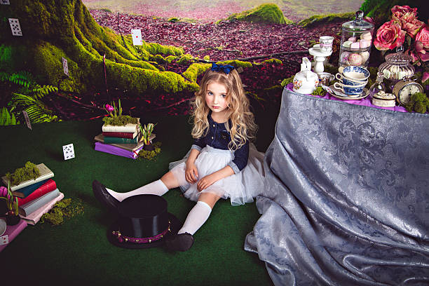 Little sitting on the floor girl as Alice in Wonderland stock photo
