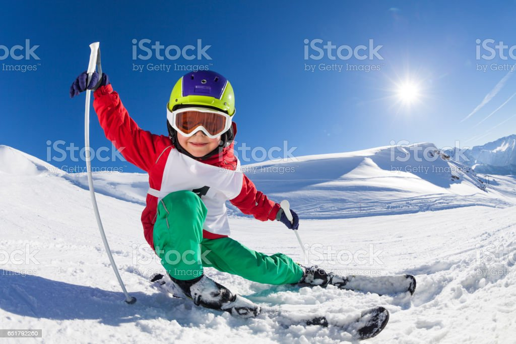 Little skier having fun at sunny snowy day stock photo