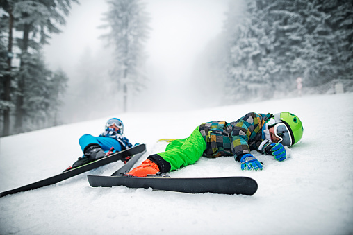 Little skiers lying on slope after crashing