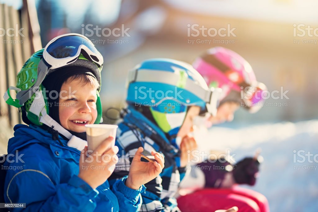 Little skiers resting on a beautiful winter day stock photo