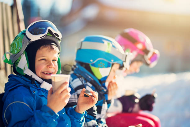 Little skiers resting on a beautiful winter day Children skiing on a winter day. Kids are taking a break in skiing and having some hot tea and cookies.  ski stock pictures, royalty-free photos & images