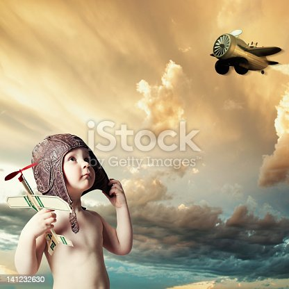 LIttle boy in the pilot`s hat with airplane. Tonality is added.