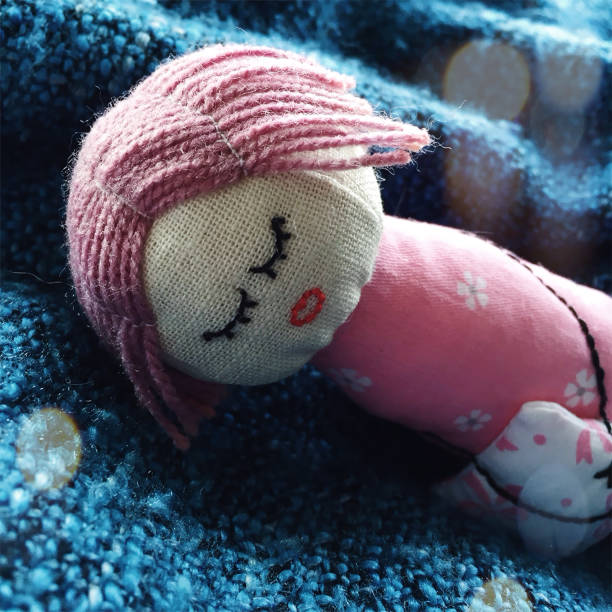 Petite poupée à la main de couchage fait de lin et de coton couché sur un plaid bleu - Photo