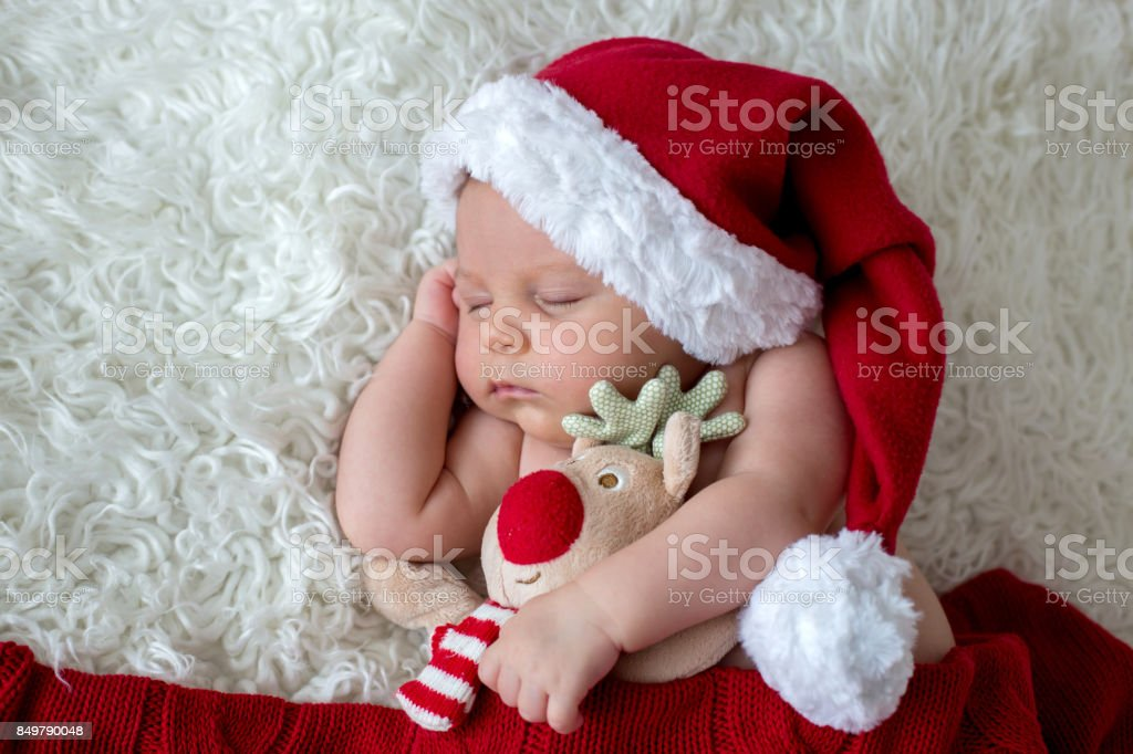Little sleeping newborn baby boy, wearing Santa hat Little sleeping newborn baby boy, wearing Santa hat and pants, holding toy Adult Stock Photo