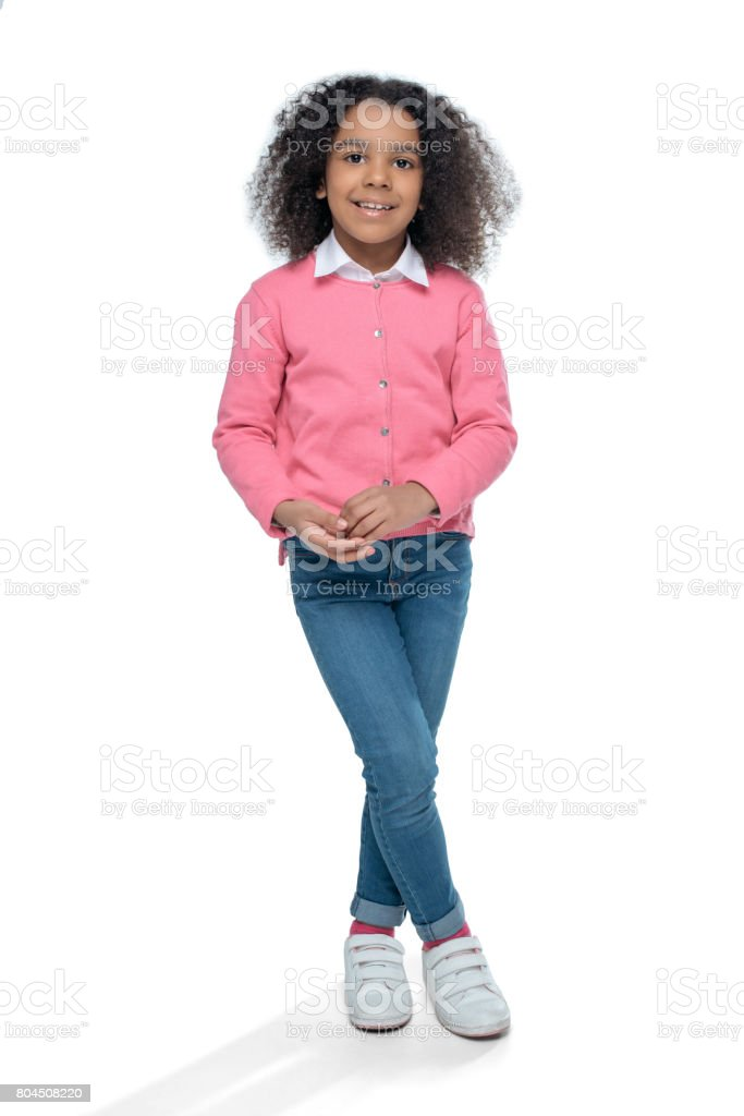 little smiling african american girl posing in pink cardigan isolated on white stock photo