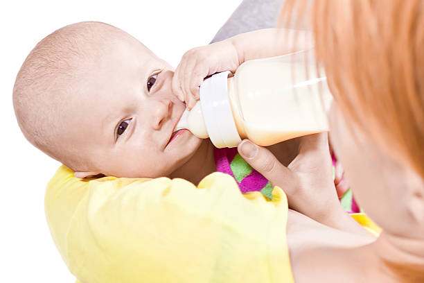 Little smiling baby with a bottle stock photo
