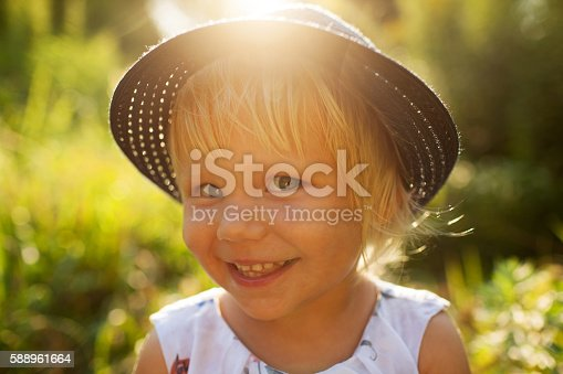 istock Little smiling blonde girl 588961664