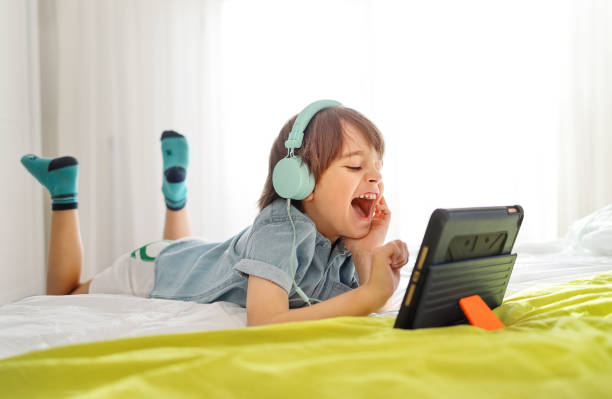 Little smiling boy wearing headphones and using tablet having fun online with his friends in a video call stock photo