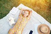 Adorable little girl relax in the park outdoors on picnic lying on blanket
