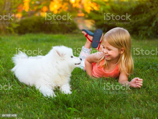 Little smiling girl playing with samoyed puppy in garden picture id641681406?b=1&k=6&m=641681406&s=612x612&h=uxs4kffr9lzcms1iyqaiknwidrxbcruynjp1z vrklc=
