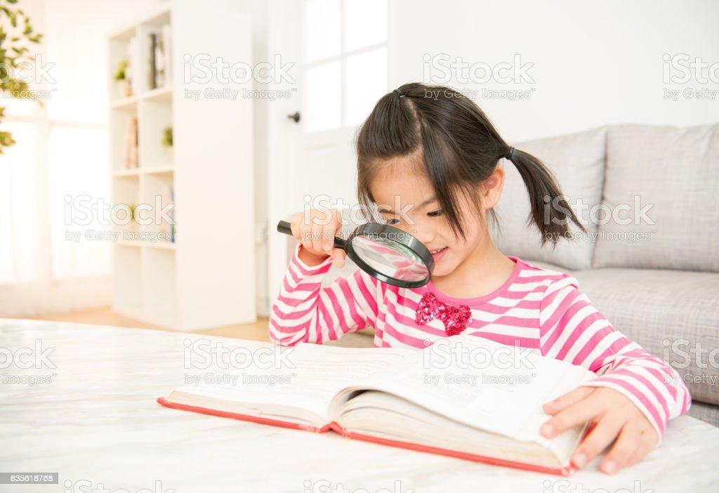 Menina sorridente, lendo um livro - foto de acervo