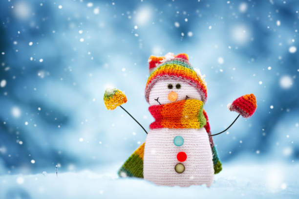 little snowman on soft snow on blue background stock photo