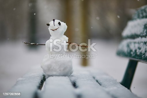 Little snowman with happy face on a bench covered with snow. Winter activites with kids. Cold snowy weather