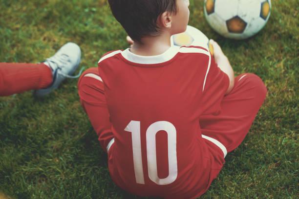 Little soccer forward player boy sitting on grass stock photo