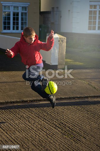 little boy play soccer in the winter morning, free style