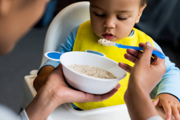 little son eating porridge - nutrire foto e immagini stock