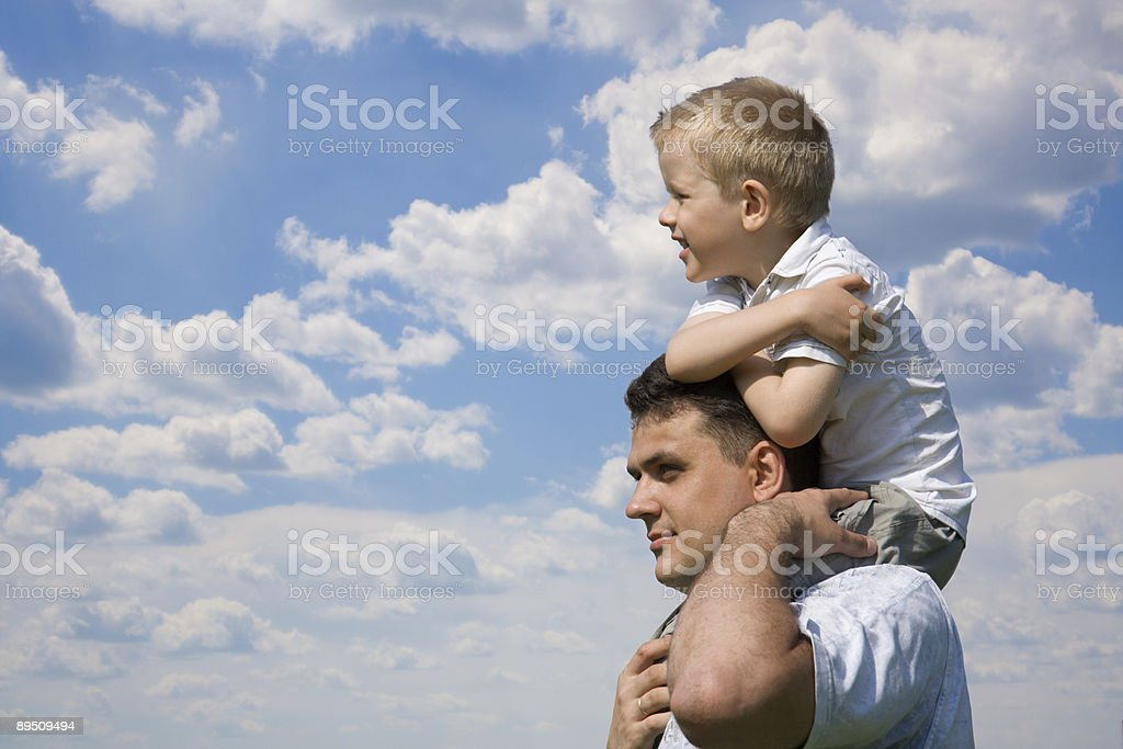 Little son sits on father`s shoulders royalty-free stock photo