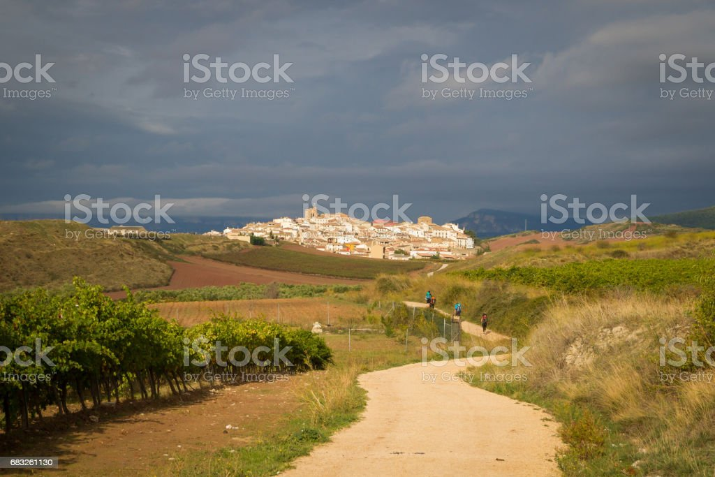 Little Spanish village glows in the sun with dark looming storm clouds stock photo