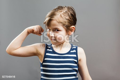 Little Sportive Tough Boy in striped  muscle shirt, showing his muscles, smiling in Camera
