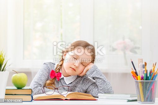 istock Little student girl sitting at the table, fell asleep at the books. Blurred background. The concept of education and school. 1150916390