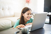 Cute latin girl smiling and sitting at home using a laptop computer to do her class work and browse the internet