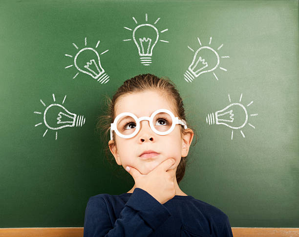 little student little girl thinking in front of the blackboard with light bulbs above her head child prodigy stock pictures, royalty-free photos & images