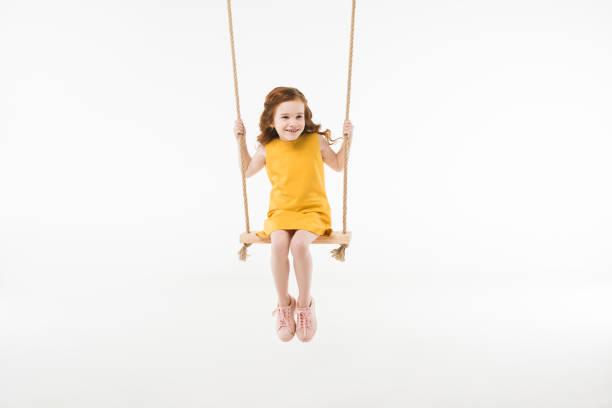 little stylish child in dress riding on swing isolated on white - balouço imagens e fotografias de stock