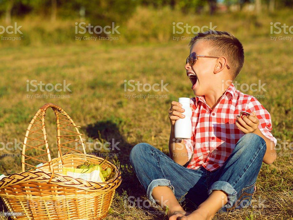 Little stylish kid having fun on the picnic drinking yogurt stock photo