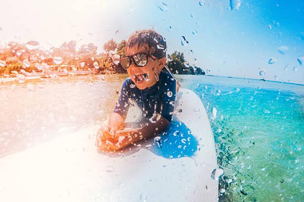 little surfer boy - wassersport stock-fotos und bilder