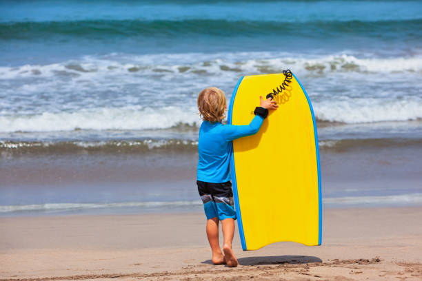Little surfer run with bodyboard on sea beach stock photo